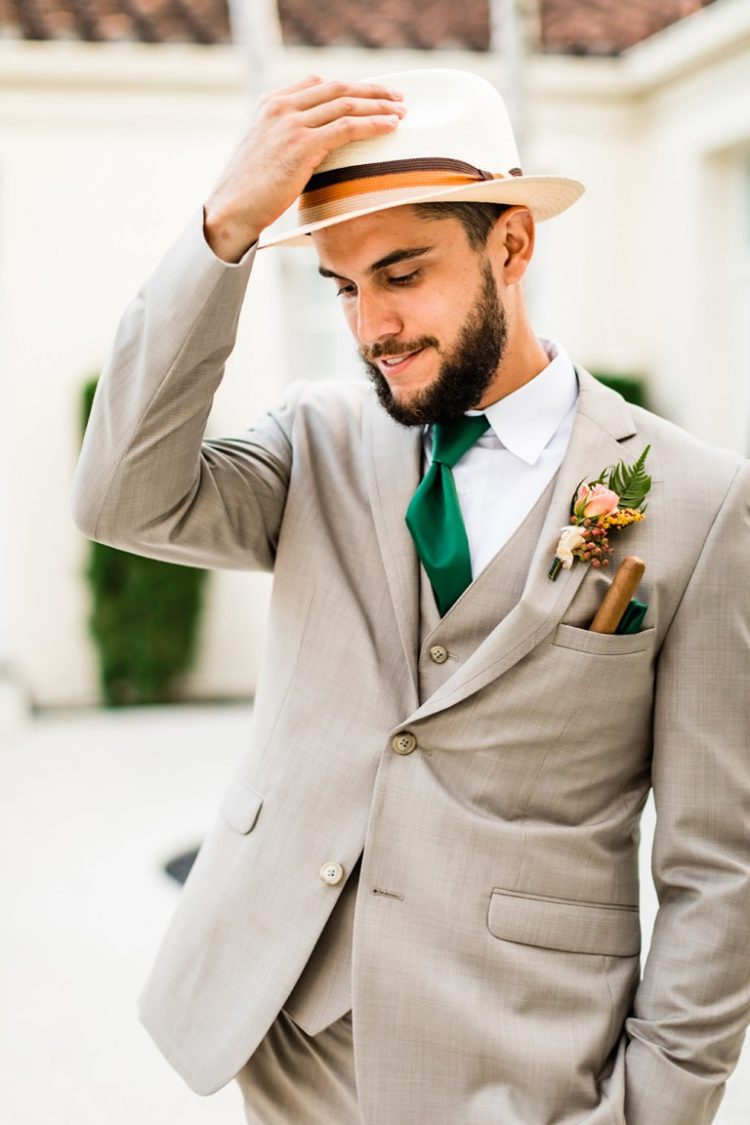 The groom was wearing a grey three-piece suit, an emerald tie and a hat, his pocket was accented with a cigar