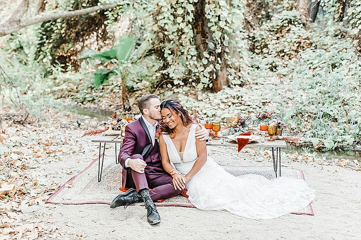 The groom was wearing a purple tux with black lapels, and the bride was wearing a sleeveless embellished plunging neckline wedding dress