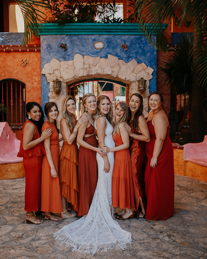The bridesmaids were wearing orange, rust and red mismatching dresses and sandals