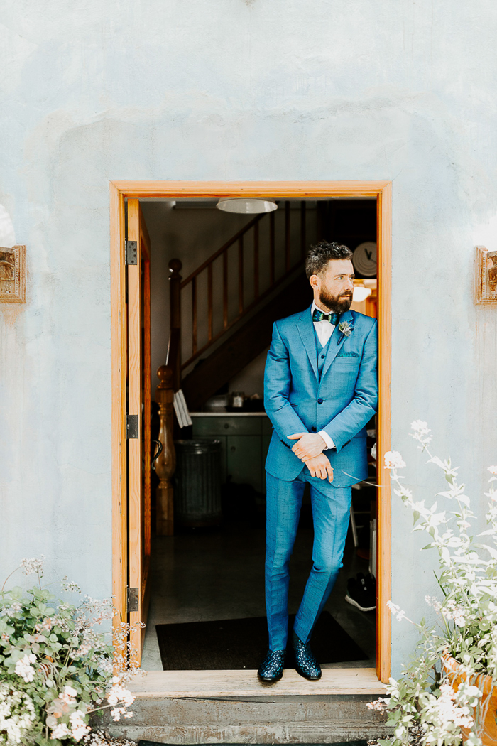 The groom was wearing a blue suit, bold printed boots, a peacock bow tie