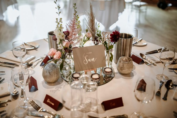 The tables were elegantly decorated with burgundy and blush blooms, herbs, candles and burgundy cards