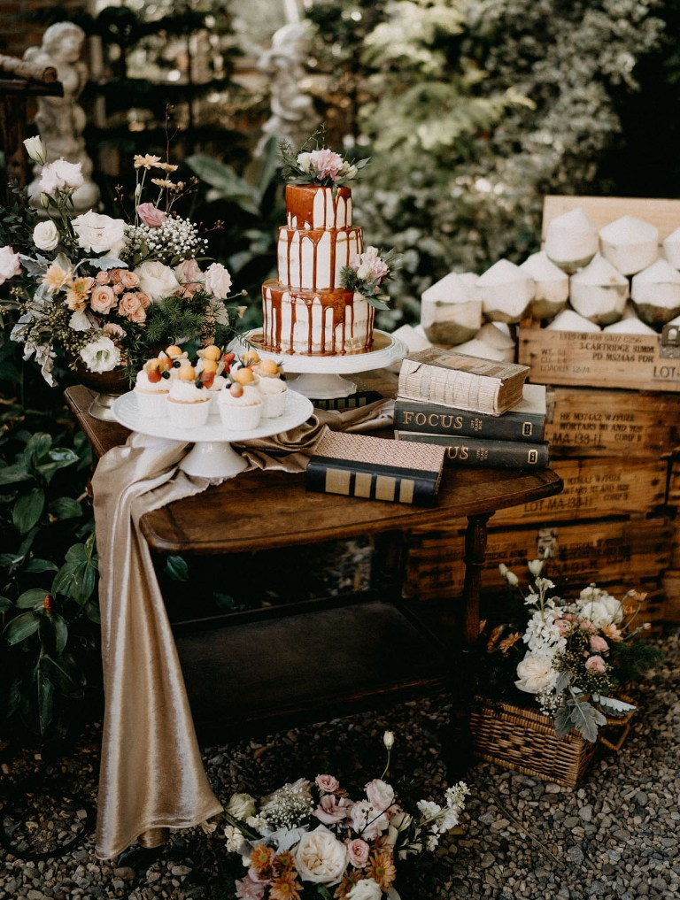 The wedding dessert table was done with pastel and white blooms, there were delicious cupcakes and a beautiful naked cake with caramel drip served