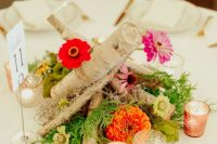 08 The wedding centerpiece was done with bright blooms, greenery and firewood and candles around
