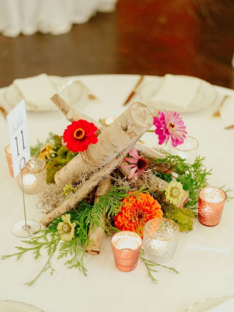 The wedding centerpiece was done with bright blooms, greenery and firewood and candles around