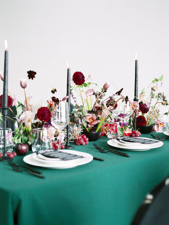 The wedding tablescape was done with an emerald tablecloth, black candles, jewel tone blooms and fresh fruit on the table