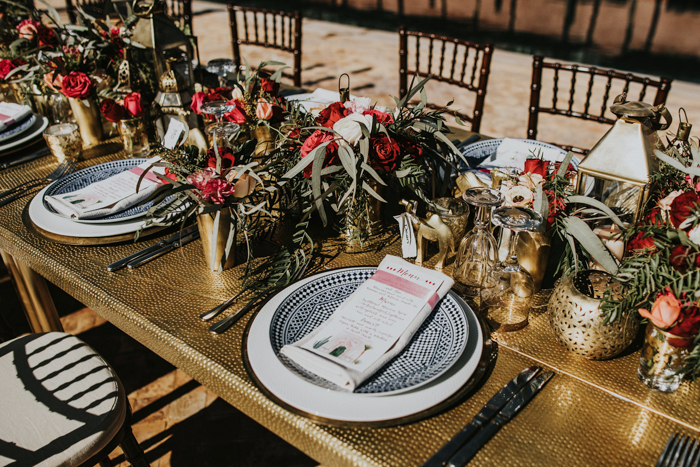 The wedding tablescapes were done with hammered tables, bright blooms and greenery and printed plates