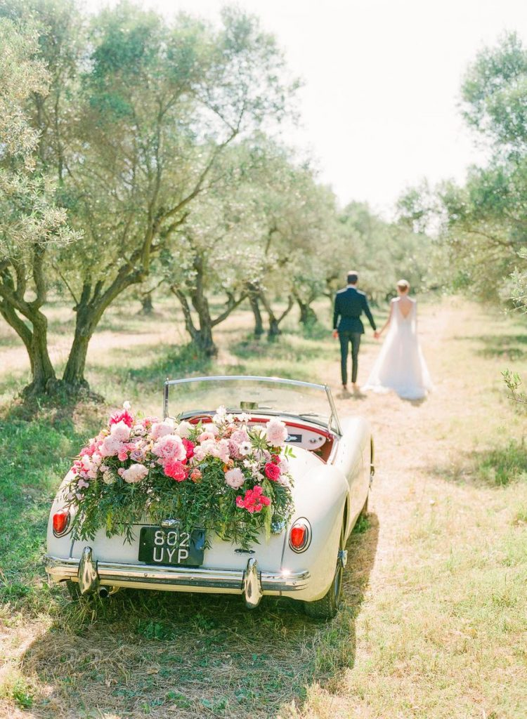 The getaway car was done with lush florals and greenery and looked amazing