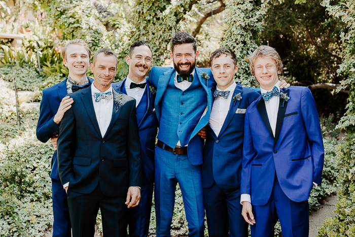 The groomsmen were rocking mismatching bold blue suits and peacock bow ties