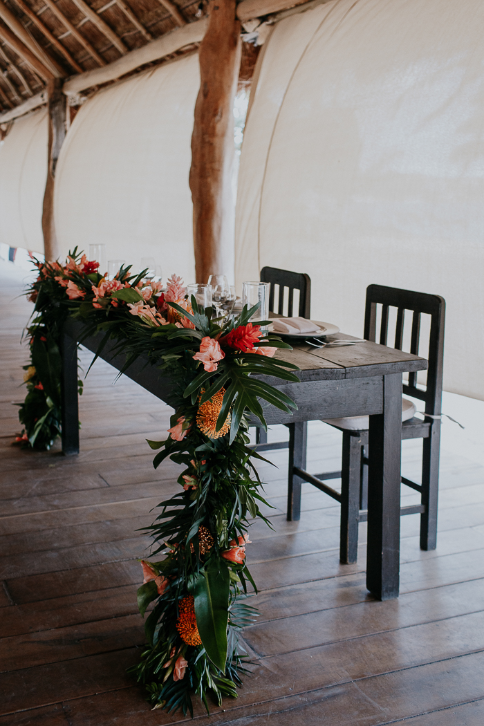 The sweetheart table was uncovered, with lush leaf garlands and bold blooms and candles