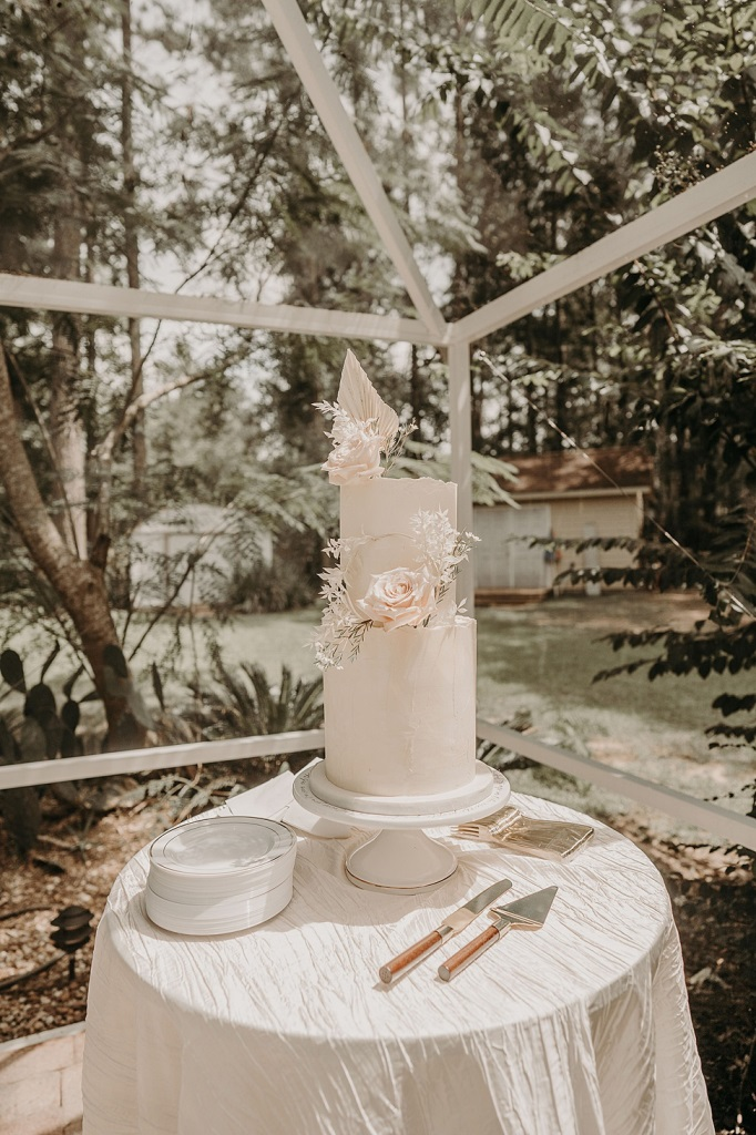 The wedding cake was a blush one, with a raw hem, white fronds and greenery plus blush roses