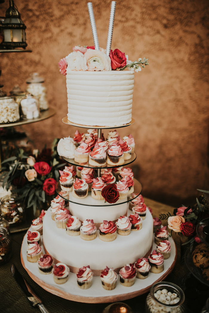 The wedding cake was a white one with bright blooms on top and bright cupcakes with frosting
