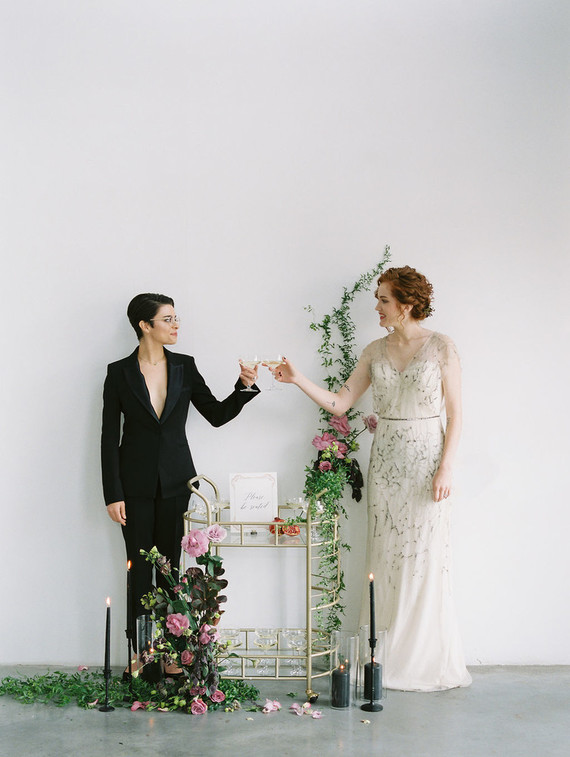 There was a bar cart decorated with lush greenery and pink blooms and black candles around