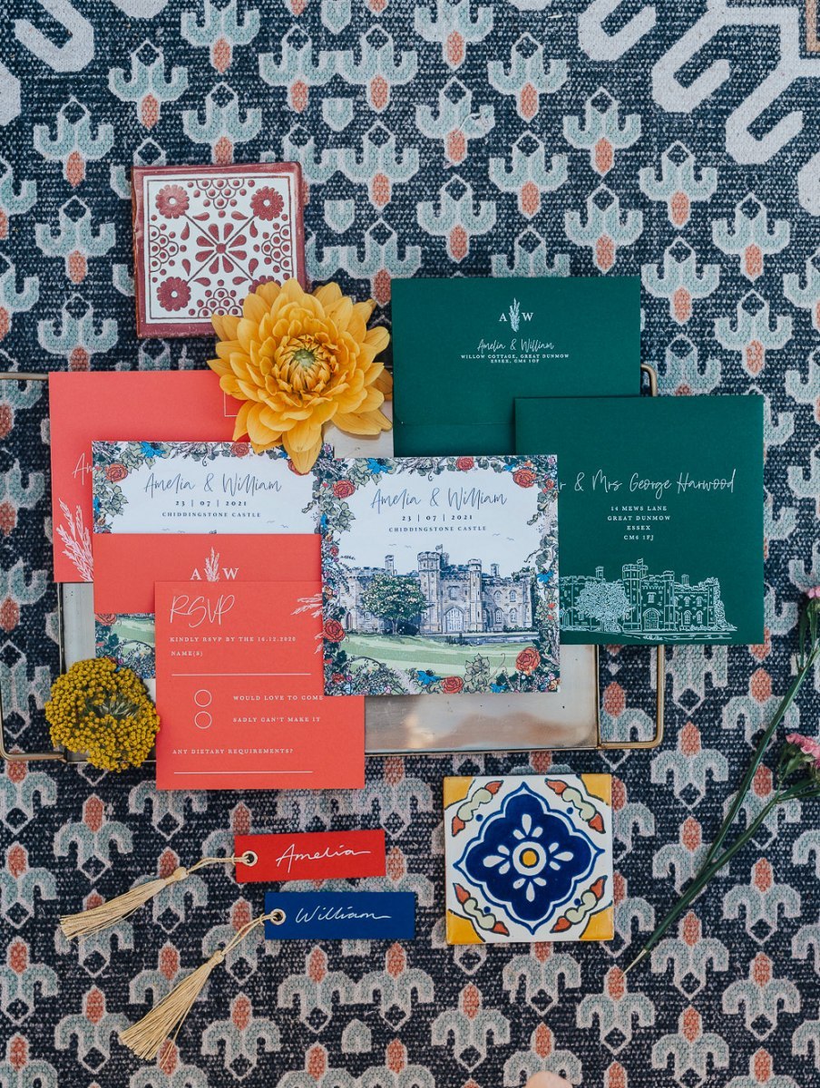 This invitation suite includes orange, hunter green and floral cards and azulejo tiles