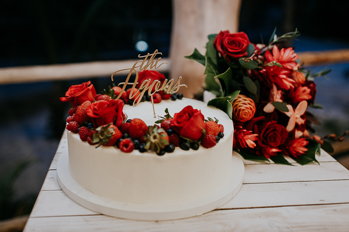 The wedding cake was a white one, with red roses and fresh berries plus a calligraphy topper