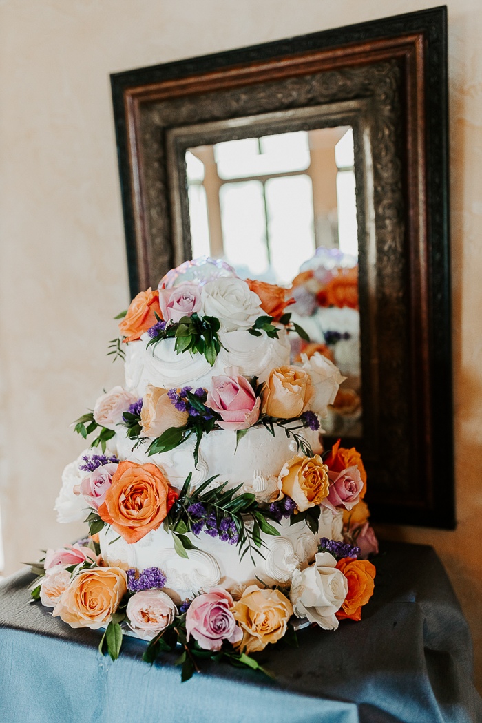 The gorgeous bright wedding cake was accented with orange, blush and white flowers and lavender