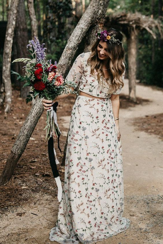 a boho two piece wedding dress with a crop top and an A-line skirt with a train all covered with wildflower embroidery