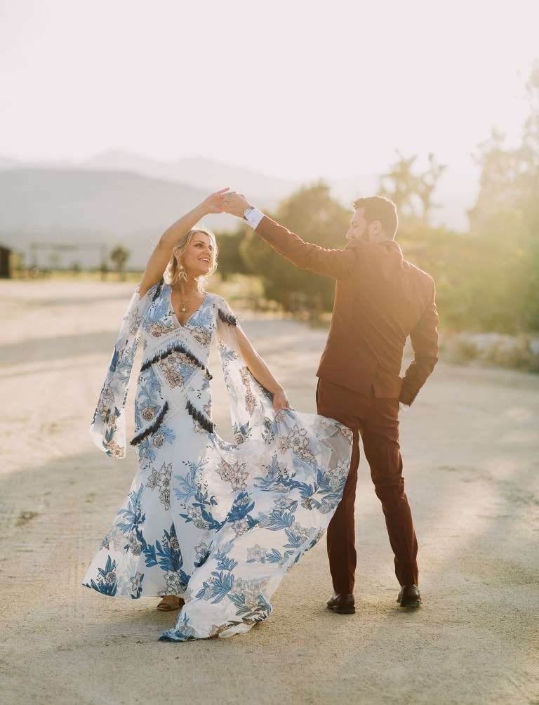 a bold blue boho floral embroidery wedding dress with cut bell sleeves, tassels and a train is a chic option