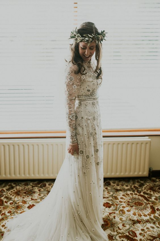 a delicate boho wedding dress with neutral and silver floral embroidery, long sleeves and embellishments looks chic