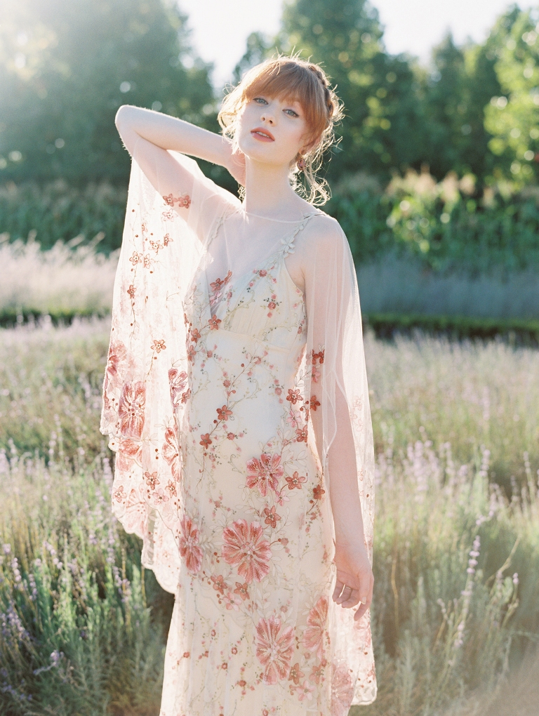 a delicate wedding dress in neutral shades with pink floral embroidery all over the dress and with a neutral underdress