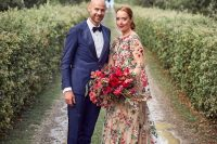 a jaw-dropping nude A-line wedding dress with bell sleeves with bold burgundy and blush floral embroidery all over the dress