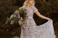 a neutral A-line wedding dress with colorful floral embroidery all over and short sleeves plus a floral crown