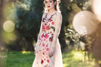 a nude lace A-line wedding dress with colorful floral embroidery on the front, paired with a dark lip for an edgy bridal look