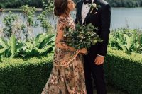 a tan A-line wedding dress with bright floral embroidery, bell sleeves and a high neckline just takes your breath away