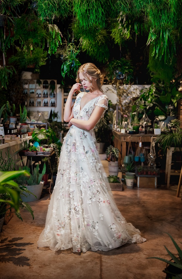a very romantic A line wedding dress with subtle pink and white floral embroidery for a delicate and enchanting bridal look