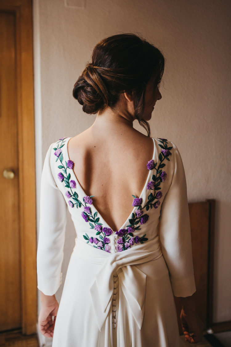 a wedding dress featuring purple and lilac embroidered flowers and leaves, a cutout back on buttons and a long train