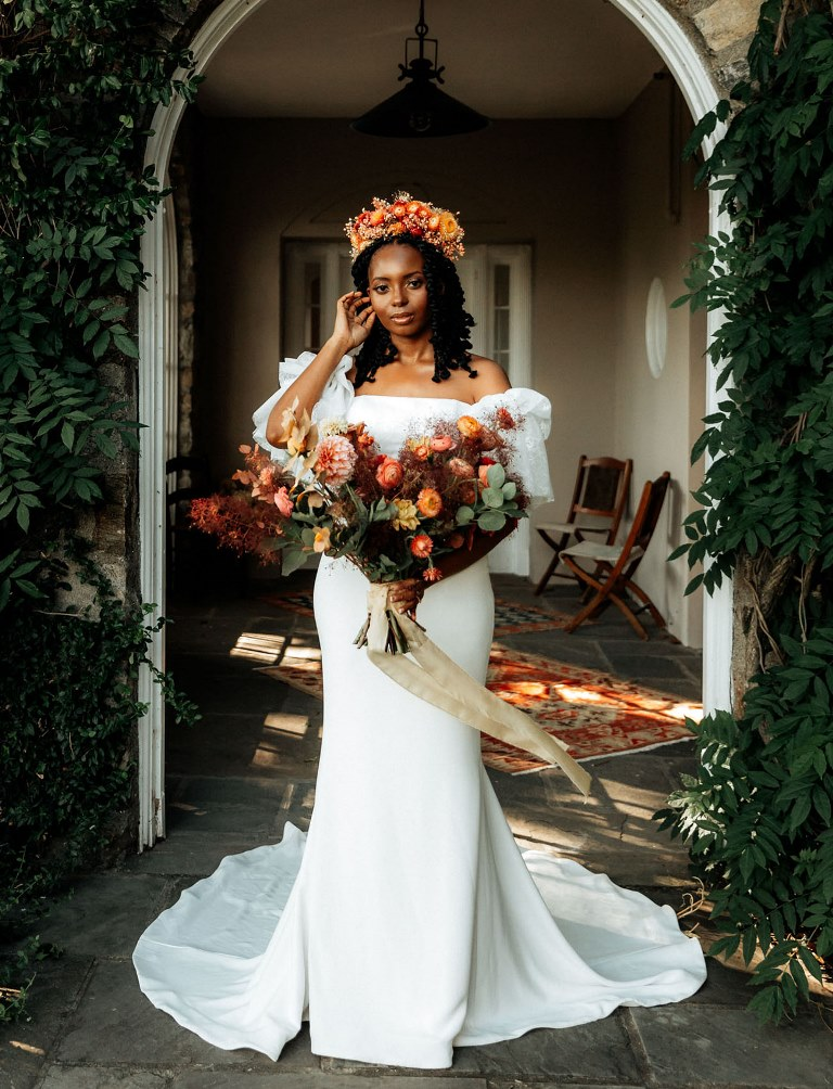 The bride was wearing a breathtaking classic sheath wedding dress with a train with catchy sleeves and a bold floral crown