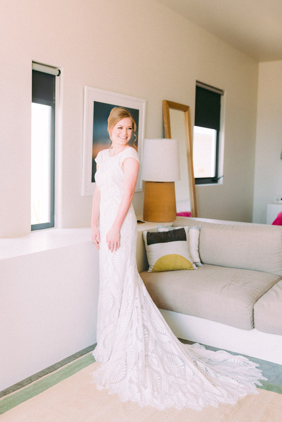 The bride was wearing a stylish cap sleeve sheath wedding dress of lace, with a high neckline and a train plus an updo