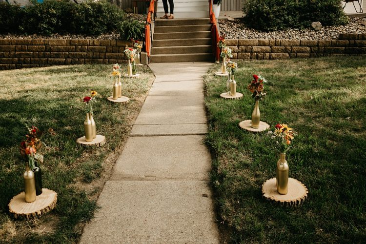 The ceremony took place on the couple's front porch, the path was lined with blooms in gold bottles