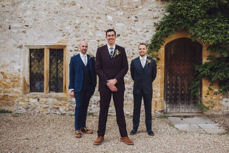 The groom was wearing a burdungy suit, a floral tie and brown shoes, his groomsmen were rocking mismatching navy suits