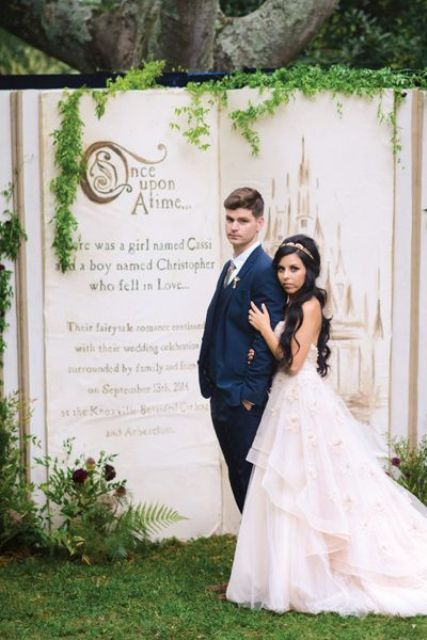a fairy tale book with greenery and blooms as a wedding backdrop for a fairy tale wedding is perfection