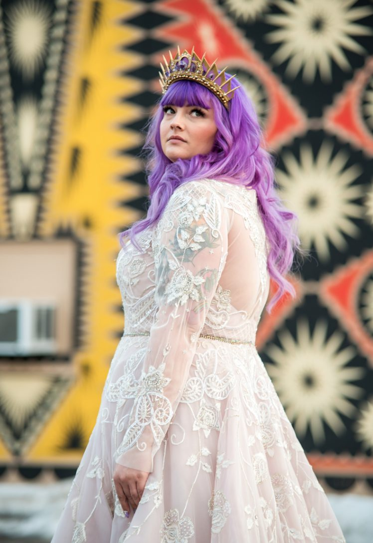 The bride was wearing a beautiful blush A-line wedding dress with lace appliques, purple hair and a gorgeous purple and gold crown