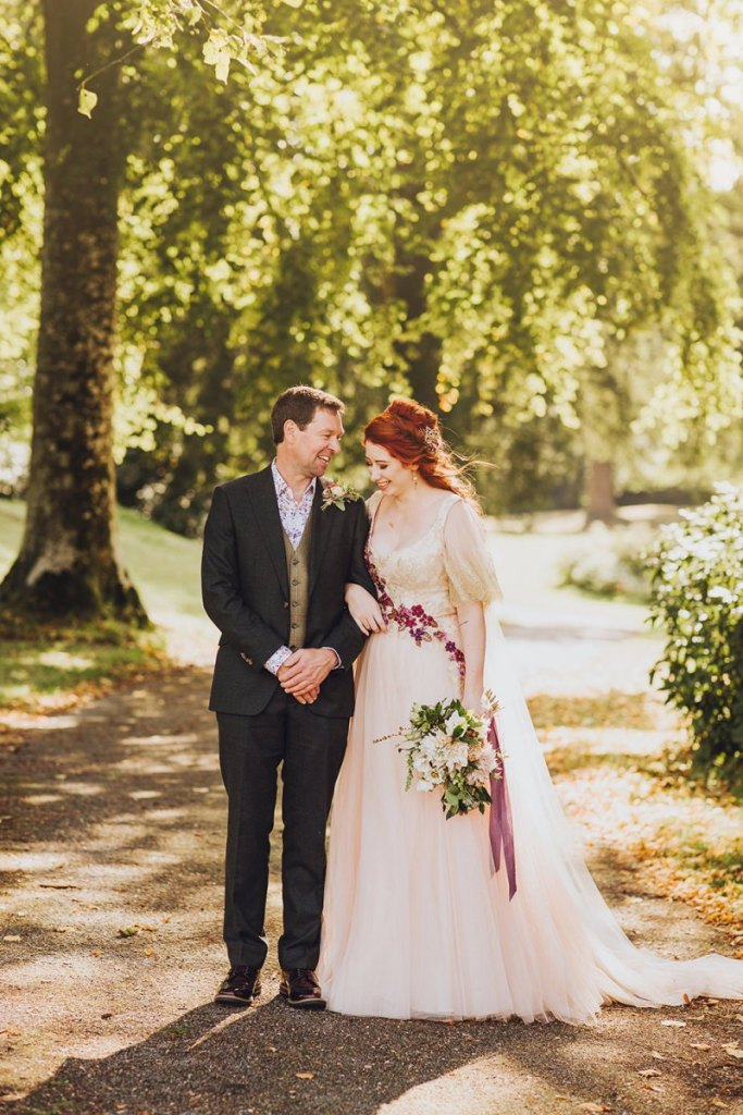 The bride was wearing a blush wedding dress with a lace embroidered bodice and burgundy floral embroidery, a deep neckline and a half updo