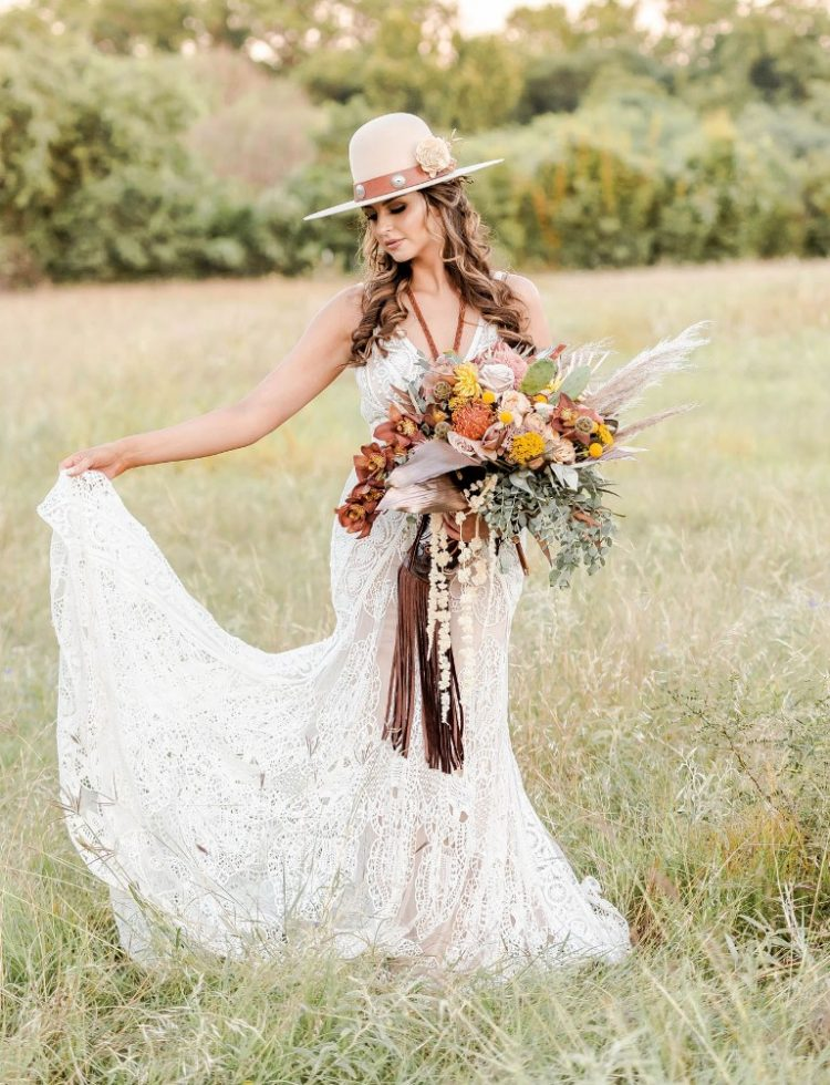 The bride was wearing a crochet lace wedding dress with a train and a wavy half updo