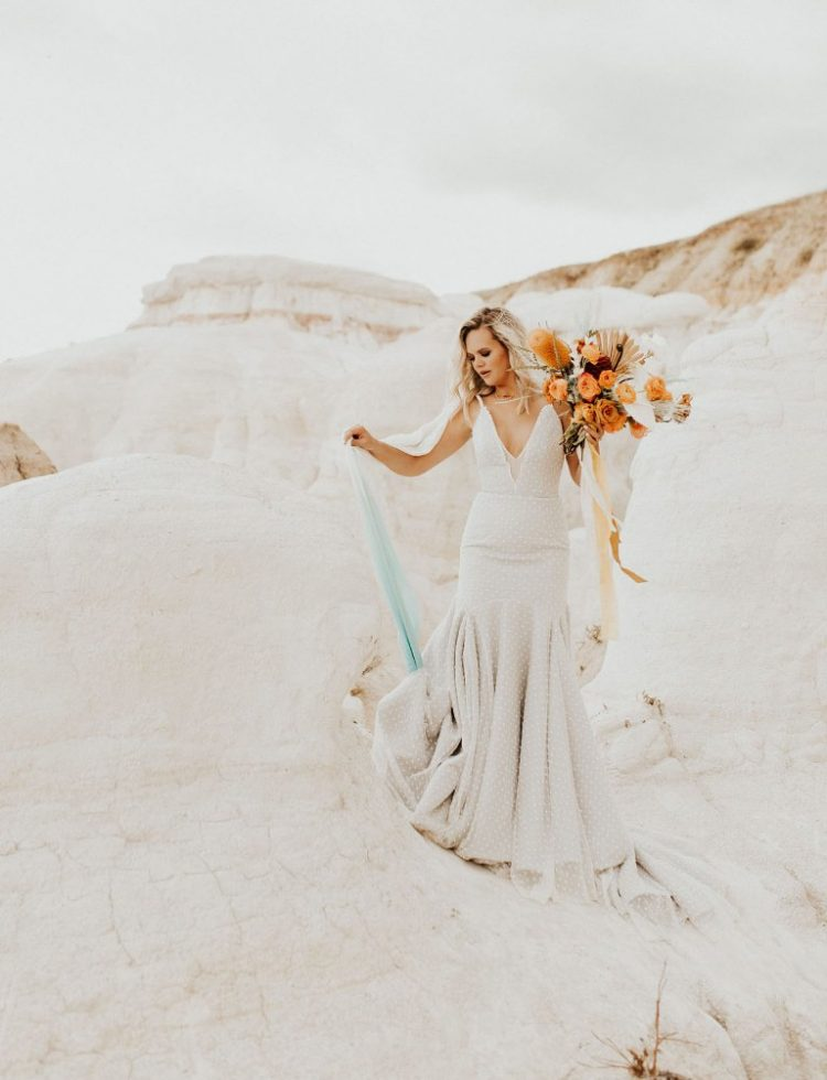 The bride was wearing a gorgeous polka dot mermaid wedding dress with a plunging neckline and straps and an ombre veil
