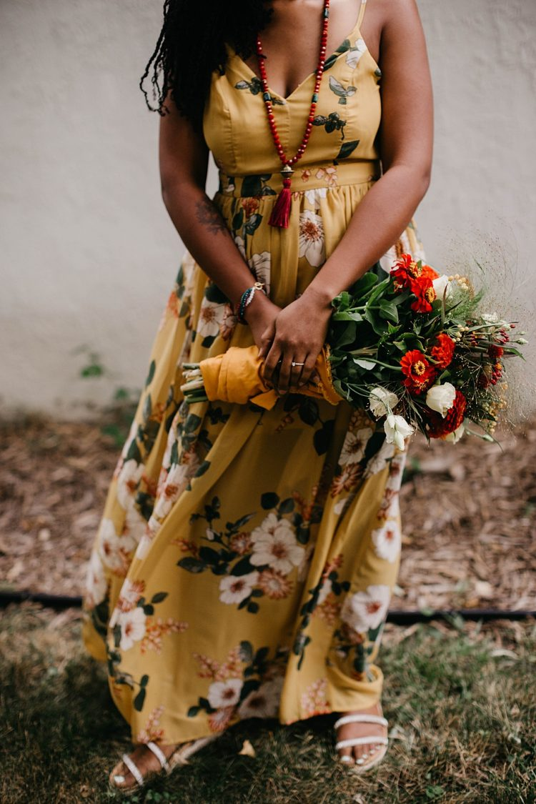 The bride was wearing a yellow floral A-line maxi dress, a colorful veil and a necklace
