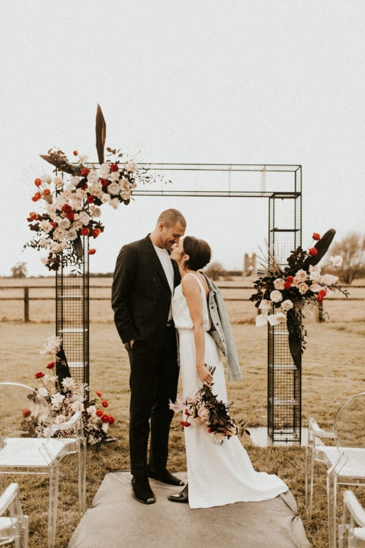 The metal wedding arch was decorated with blush and red blooms and dark leaves