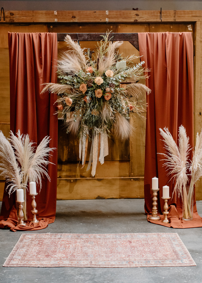 The wedding arch was done with burgundy curtains, candles, pampas grass and a lush floral arrangement with bright blooms and greenery