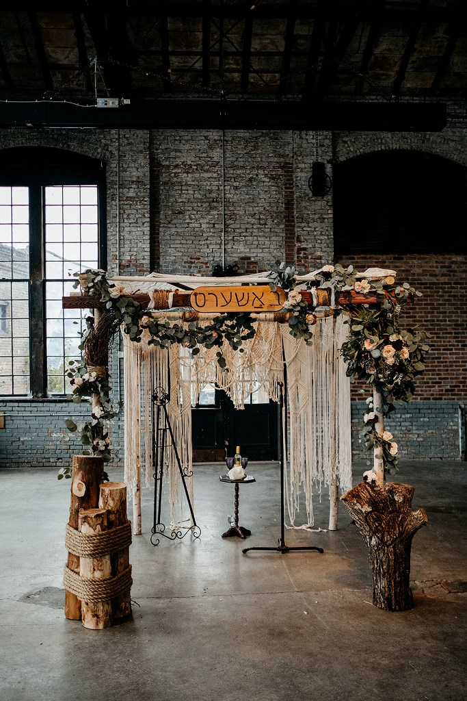 The wedding arch was done with macrame, greenery, a sign and with tree sutmps around