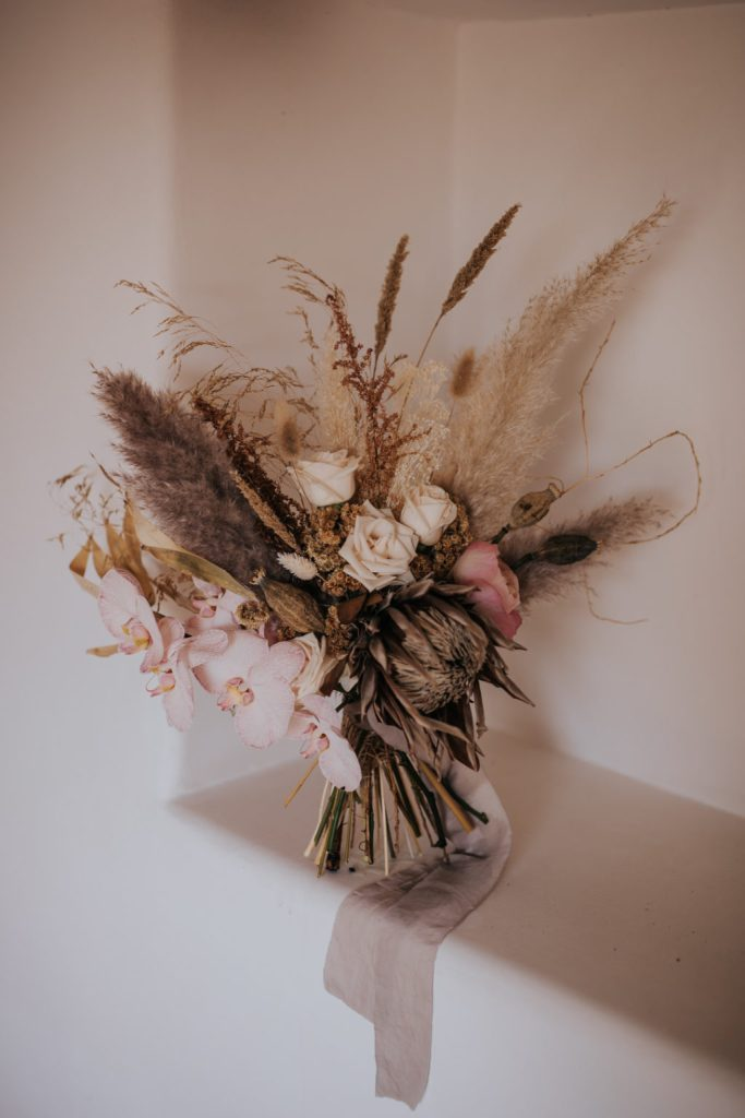 The wedding bouquet was with blush and pink blooms and lots of dried elements and ribbons