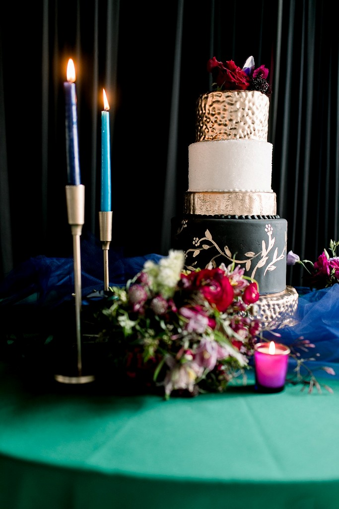 The wedding cake was done in white, gold and black plus bright blooms and gems