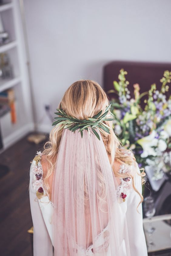 a boho wedding dress decorated with blooms and a blush veil attached to a greenery halo look fantastic