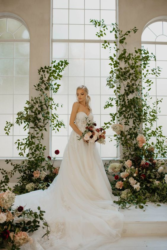 a fairy-tale wedding altar of greenery with white, blush and burgundy blooms is very sophisticated and chic