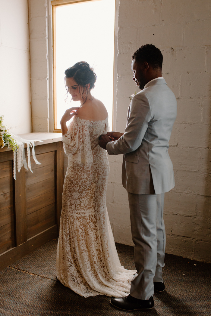 The bride was wearing an off the shoulder lace sheath wedding dress with a train, the groom was rocking a grey suit with a neutral tie
