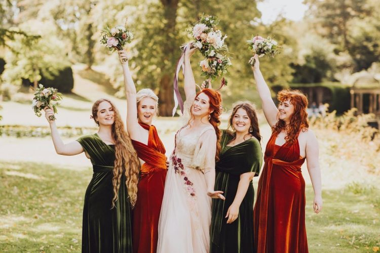 The bridesmaids were wearing mismatching velvet dresses in orange and green
