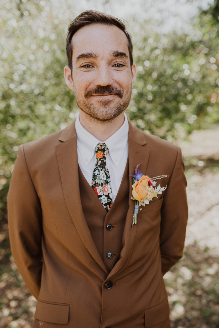 The groom was wearing a brown suit with a floral tie and boutonniere