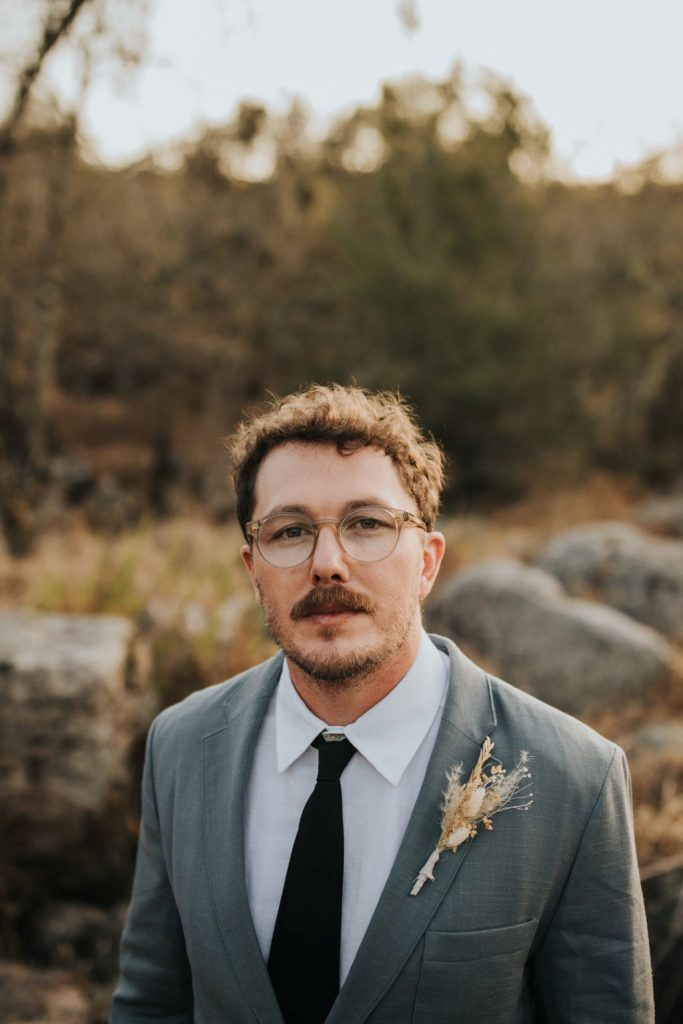 The groom was wearing a grey suit, a black tie and a dried flower boutonniere